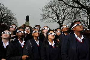 LONDON, UNITED KINGDOM - MARCH 20:  Local school kids wear protective glasses to watch a partial solar eclipse from Greenwich park on March 20, 2015. A partial eclipse of varying degrees was visible, depending on weather conditions, across most of Europe, northern Africa, northwest Asia and the Middle East, before finishing its show close to the North Pole.  (Photo by Joseph Okpako/Getty Images)