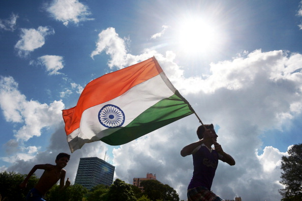 """Indian youths run in a field with their national flag as the country celebrates its 67th Independence Day in Kolkata on August 15, 2013. Premier Manmohan Singh warned Pakistan August 15 against using its soil for """"anti-India activity"""", following a fresh escalation of tensions between the nuclear-armed neighbours over a deadly attack on Indian soldiers. AFP PHOTO/Dibyangshu SARKAR        (Photo credit should read DIBYANGSHU SARKAR/AFP/Getty Images)"""